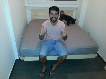 לקוח יושב על מזרן ובסיס מיטה שנרכש במפעלי טום