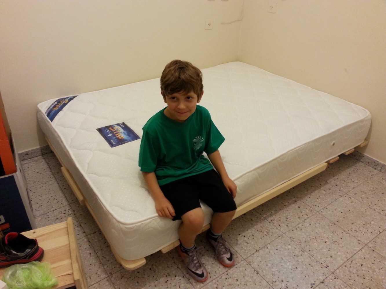 ילד יושב על מזרן שנרכש במפעלי טום