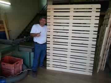 לקוח אוחז בבסיס מיטה מעץ מלא שרכש במפעלי טום
