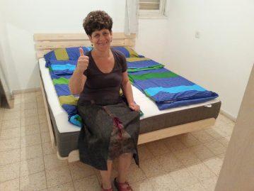 לקוחה יושבת על מזרן ובסיס מיטה שנרכשו במפעלי טום