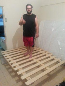 לקוח עומד על בסיס מיטה מעץ מלא שנרכש במפעלי טום