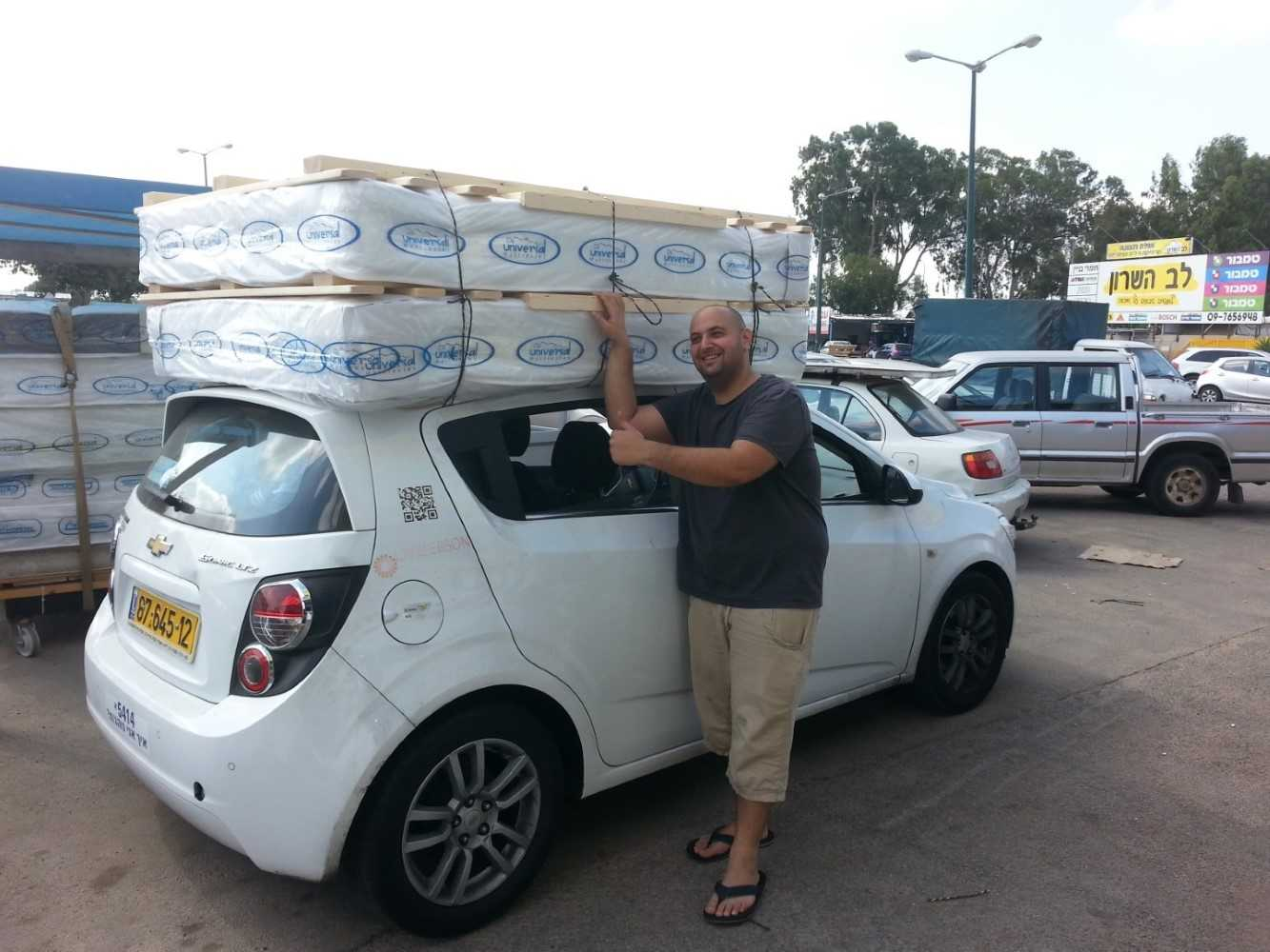 לקוח עם מזרנים ובסיסי מיטה קשורים לגג הרכב
