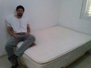 לקוח יושב על בסיס מיטה ומזרן שנרכשו במפעלי טום