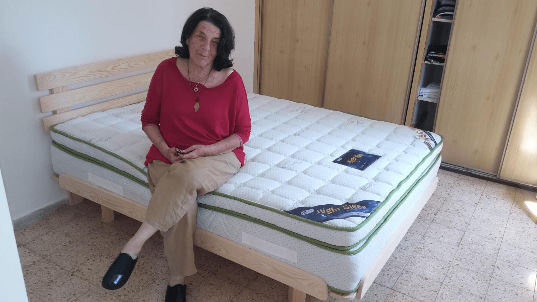 לקוחה יושבת על מזרן ובסיס מיטה