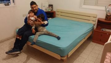 משפחה יושבת על בסיס מיטה ומזרן שנרכשו במפעלי טום