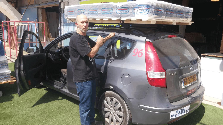 לקוח מעמיס בסיס מיטה מעץ מלא ומזרן על גג הרכב