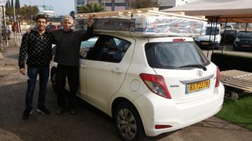 לקוחות מעמיסים בסיס מיטה מעץ מלא ומזרן על גג הרכב