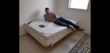 לקוח שוכב על מזרן ובסיס מיטה מעץ מלא שנרכש במפעלי טום